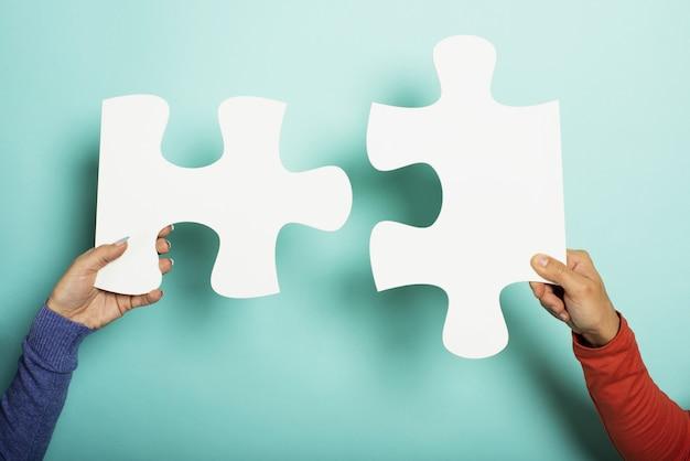 Twee volkeren voegen zich bij een puzzel op cyan. bovenaanzicht Premium Foto