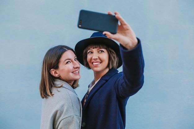 Twee vrienden buitenshuis met stijlvolle kleding die een selfie met mobiele telefoon Premium Foto