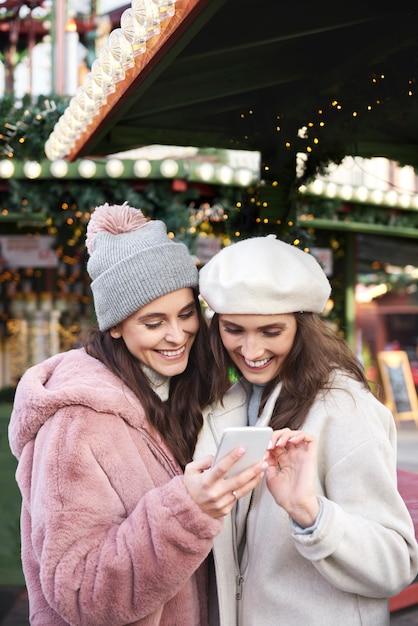 Twee vrienden die mobiele telefoon op een kerstmarkt doorbladeren Gratis Foto