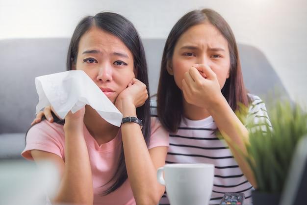 Twee vrienden kijken naar een serie film op tv en emotioneel huilen in vakantietijden in de woonkamer thuis. Premium Foto