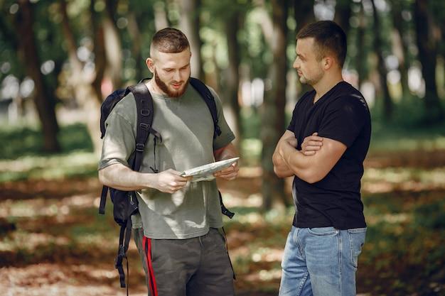 Twee vrienden rusten uit in een bos Gratis Foto