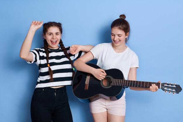Twee vrienden zingen en dansen geïsoleerd, dame met gitaar spelen, aantrekkelijk meisje in gestreept t-shirt en vlechten handen omhoog. Gratis Foto