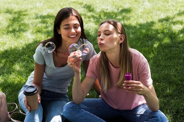 Twee vriendinnen buiten bellen blazen Gratis Foto