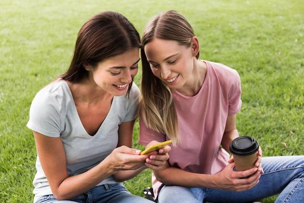 Twee vriendinnen buiten met smartphone en koffie Gratis Foto
