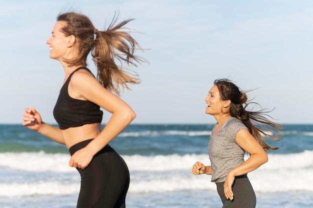 Twee vriendinnen joggen op het strand Gratis Foto