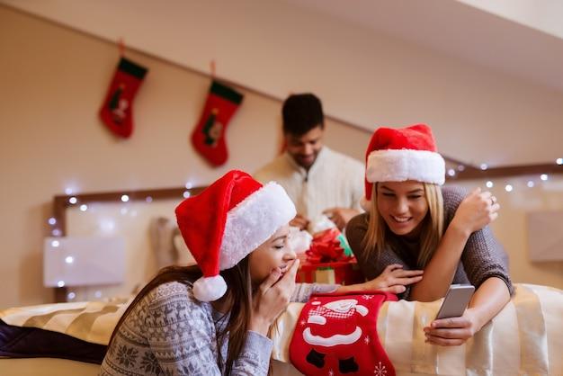 Twee vriendinnen lezen bericht terwijl hun mannelijke vriend geschenken opent Premium Foto