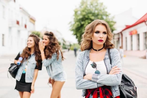 Twee vriendinnen op de achtergrond roddelen over derde tiener met make-up en kapsel wegkijken met verdriet. Premium Foto