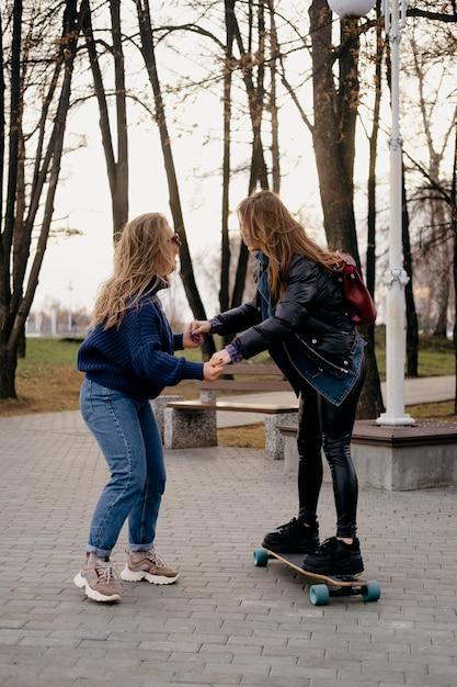 Twee vriendinnen plezier skateboarden in het park Gratis Foto