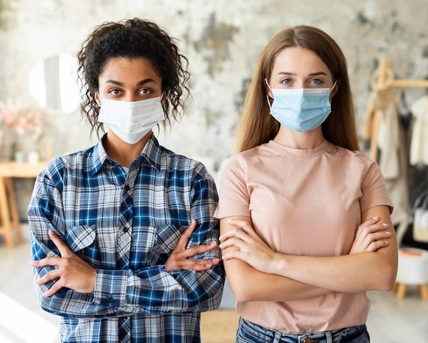 Twee vriendinnen poseren samen met medische maskers Gratis Foto