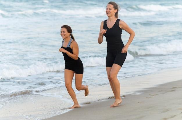 Twee vriendinnen samen joggen op het strand Gratis Foto