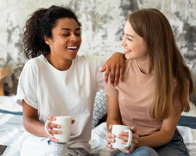 Twee vriendinnen thuis praten over koffie Gratis Foto