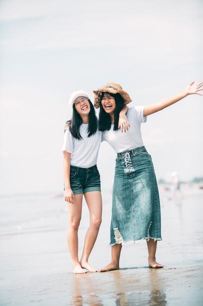 Twee vrolijk aziatisch tienergeluk op vakantie overzees strand Premium Foto