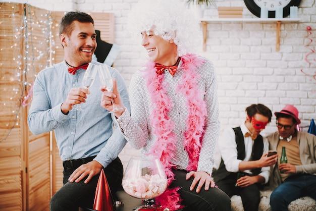 Twee vrolijke homoseksuele mannen in strikjes flirten speels op feestjes. Premium Foto