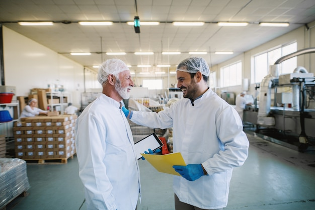 Twee vrolijke mannelijke werknemers van de voedselfabriek in steriele kleren die en over bedrijfsplannen glimlachen praten. Premium Foto