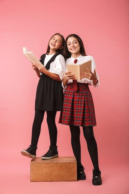 Twee vrolijke schoolmeisjes in uniform staande geïsoleerd over roze muur, met boeken Premium Foto