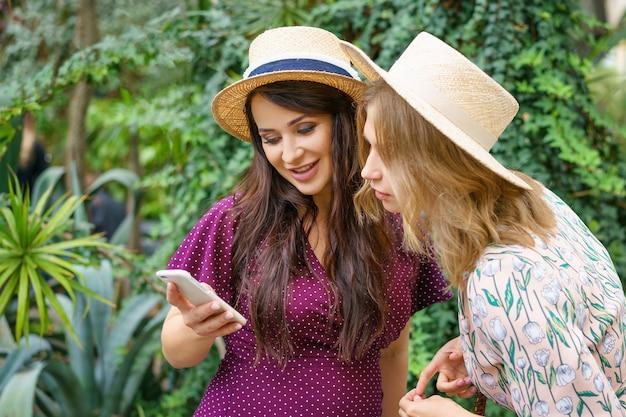 Twee vrolijke vrienden kijken naar de telefoon, maken selfie-hoeden op een groene achtergrond natuurlijk. Premium Foto