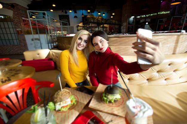 Twee vrolijke vrolijke meisjes die een selfie nemen terwijl ze samen in café zitten Premium Foto