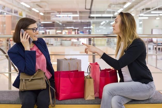Twee vrouw vrienden zitten in het winkelcentrum na het winkelen, tassen kijken, rusten. Premium Foto