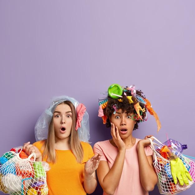 Twee vrouwelijke activisten staren stomverbaasd met omg-uitdrukking, geschokt om veel vuilnis op te halen, netzakken met plastic afval vast te houden, gekleed in vrijetijdskleding, afval ophalen voor recycling, vrije ruimte erboven Gratis Foto