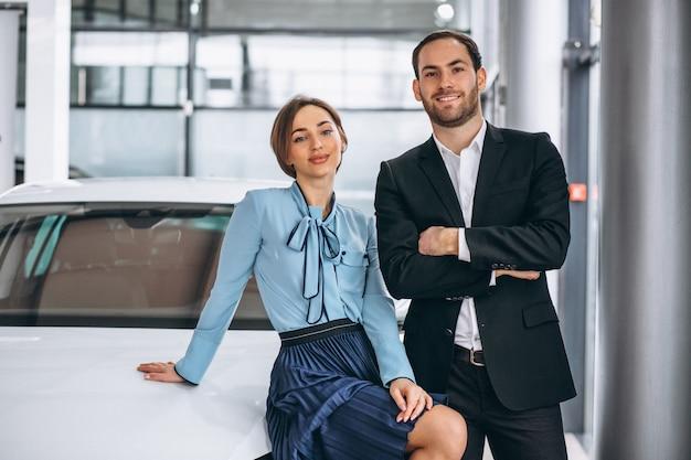 Twee vrouwelijke en mannelijke verkoper in een autoshowroom Gratis Foto