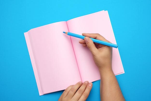 Twee vrouwelijke handen met open kladblok met lege roze lakens, bovenaanzicht Premium Foto