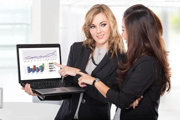 Twee vrouwelijke ondernemers bespreken iets op de laptop Premium Foto