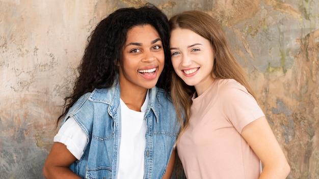 Twee vrouwelijke vrienden die en samen glimlachen stellen Gratis Foto