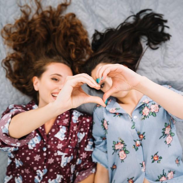 Twee vrouwelijke vrienden die hartvorm maken Gratis Foto