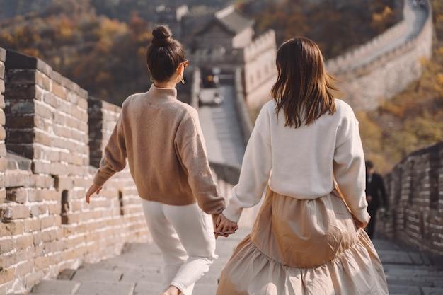 Twee vrouwelijke vrienden die langs de grote muur van china dichtbij het gevolg van peking lopen Gratis Foto
