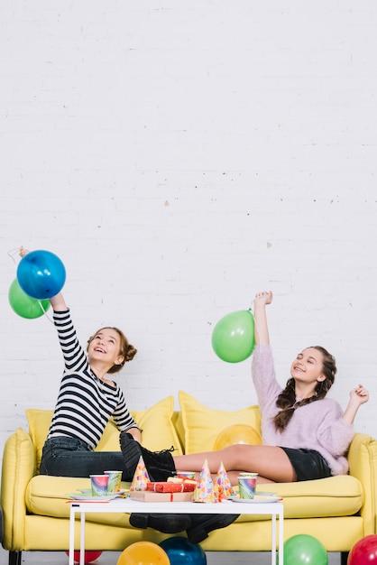 Twee vrouwelijke vrienden die op bank zitten die van de verjaardagspartij thuis genieten Gratis Foto