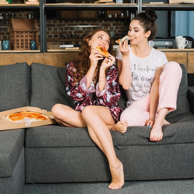 Twee vrouwelijke vrienden die pizza thuis eten Gratis Foto
