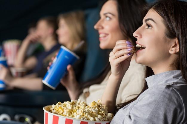 Twee vrouwelijke vrienden die samen een film bij de bioskoop letten Premium Foto
