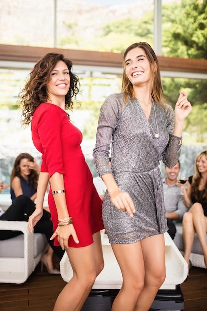 Twee vrouwen dansen en een groep vrienden kijken naar hun dans op feestje Premium Foto