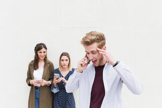 Twee vrouwen die de mens bekijken die op mobiele telefoon spreken Gratis Foto