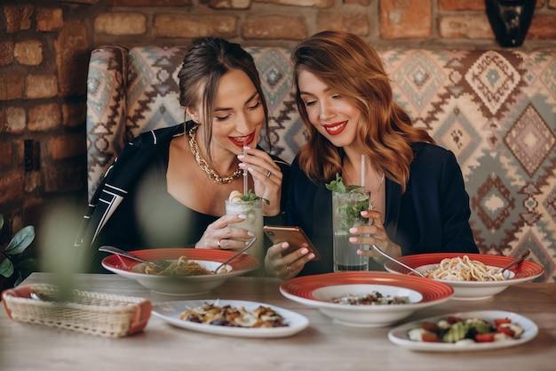 Twee vrouwen die deegwaren in een italiaans restaurant eten Gratis Foto