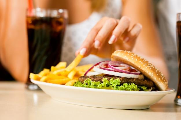 Twee vrouwen die hamburger eten en soda drinken Premium Foto