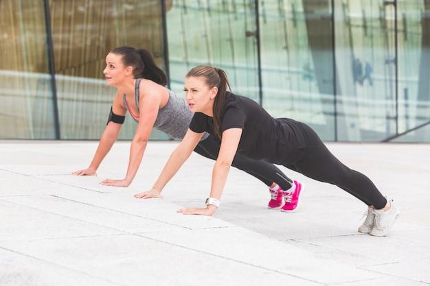 Twee vrouwen die opdrukoefeningenoefeningen doen Premium Foto