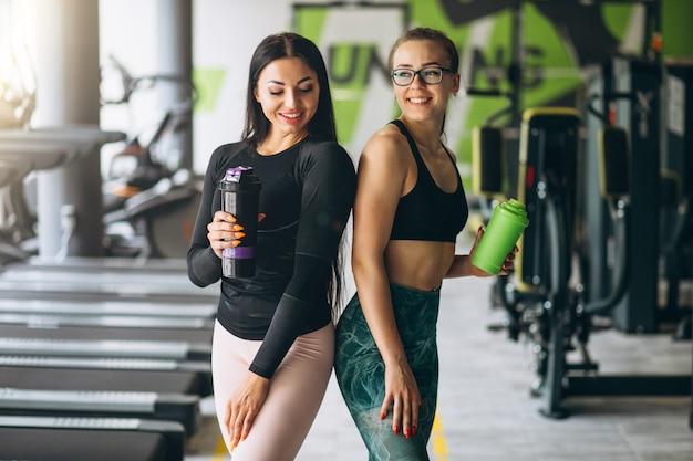 Twee vrouwen die samen bij gymnastiek opleiden Gratis Foto