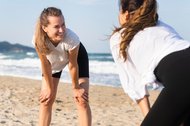 Twee vrouwen die samen op het strand oefenen Gratis Foto