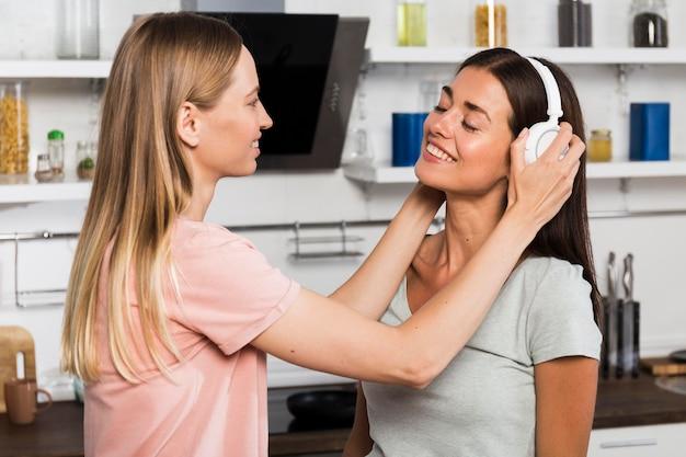 Twee vrouwen die thuis naar muziek op hoofdtelefoons luisteren Gratis Foto