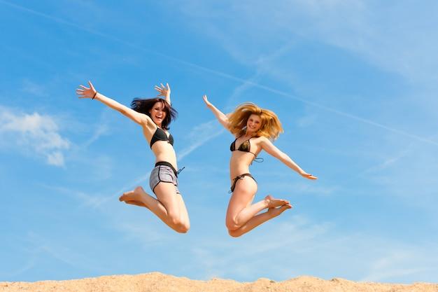Twee vrouwen in badkleding springen graag boven het zandstrand Premium Foto