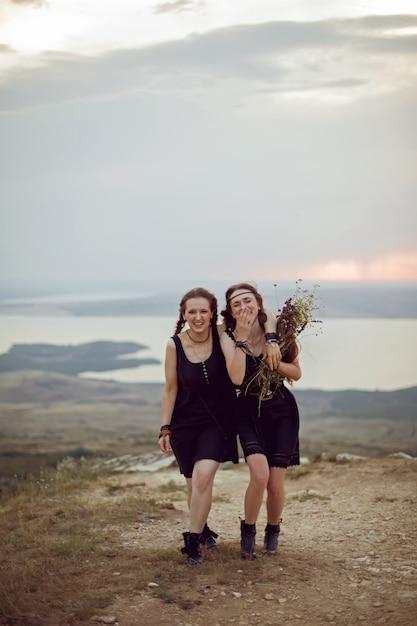 Twee vrouwen in zwarte jurken lopen op de berg met een boeket bloemen in de zomer bij zonsondergang Premium Foto