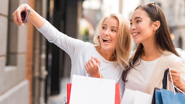 Twee vrouwen nemen selfie met veel boodschappentassen Gratis Foto