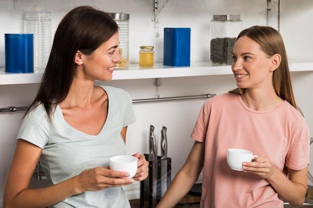 Twee vrouwen thuis in de keuken die bij koffie kletsen Gratis Foto