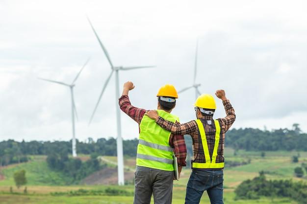 Twee windmolen ingenieur inspectie en voortgangscontrole windturbine op de bouwplaats en geslaagd in de missie. Premium Foto