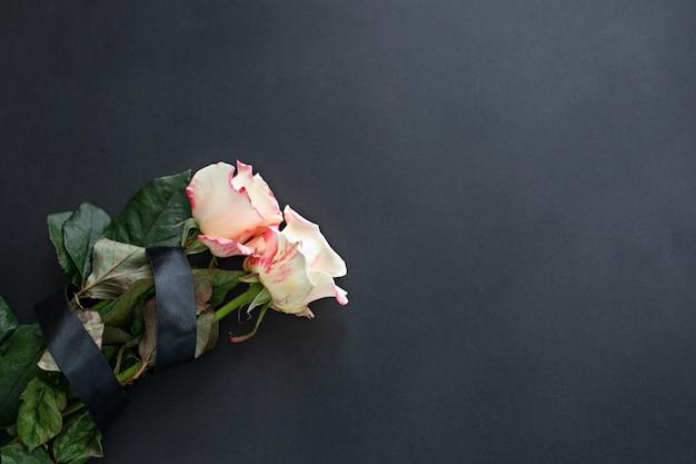 Twee wit-roze rozen op een zwarte achtergrond met copyspace Premium Foto