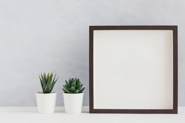 Twee witte ingemaakte cactusinstallatie met leeg wit fotokader op bureau tegen muur Gratis Foto