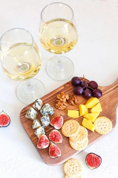 Twee witte wijnglas en kaasplank met noten Gratis Foto