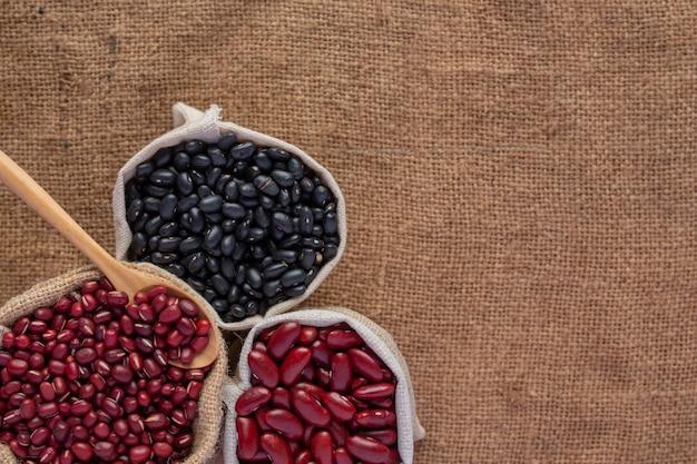 Twee zaden van de kleurenboon die op een bruine houten vloer worden geplaatst. Gratis Foto