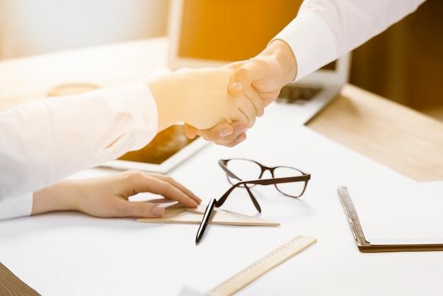 Twee zakelijke partners schudden elkaars hand op het bureau Gratis Foto